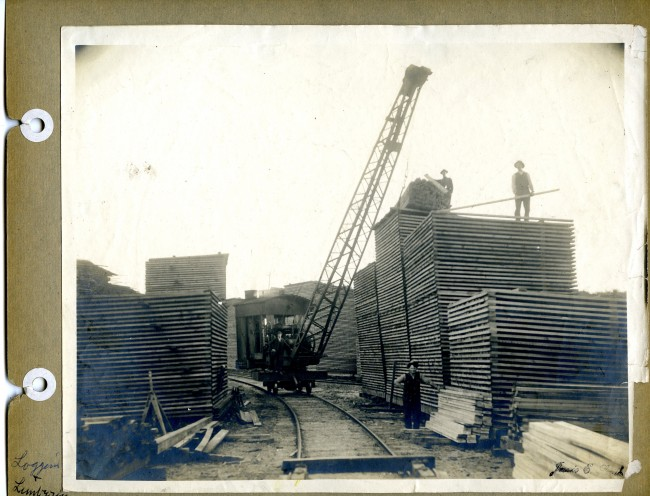 This historical photo shows a crane on rails that is used to stack piles of cut lumber into piles that appear to be over twenty feet high with workers placing the logs  on top of the stack