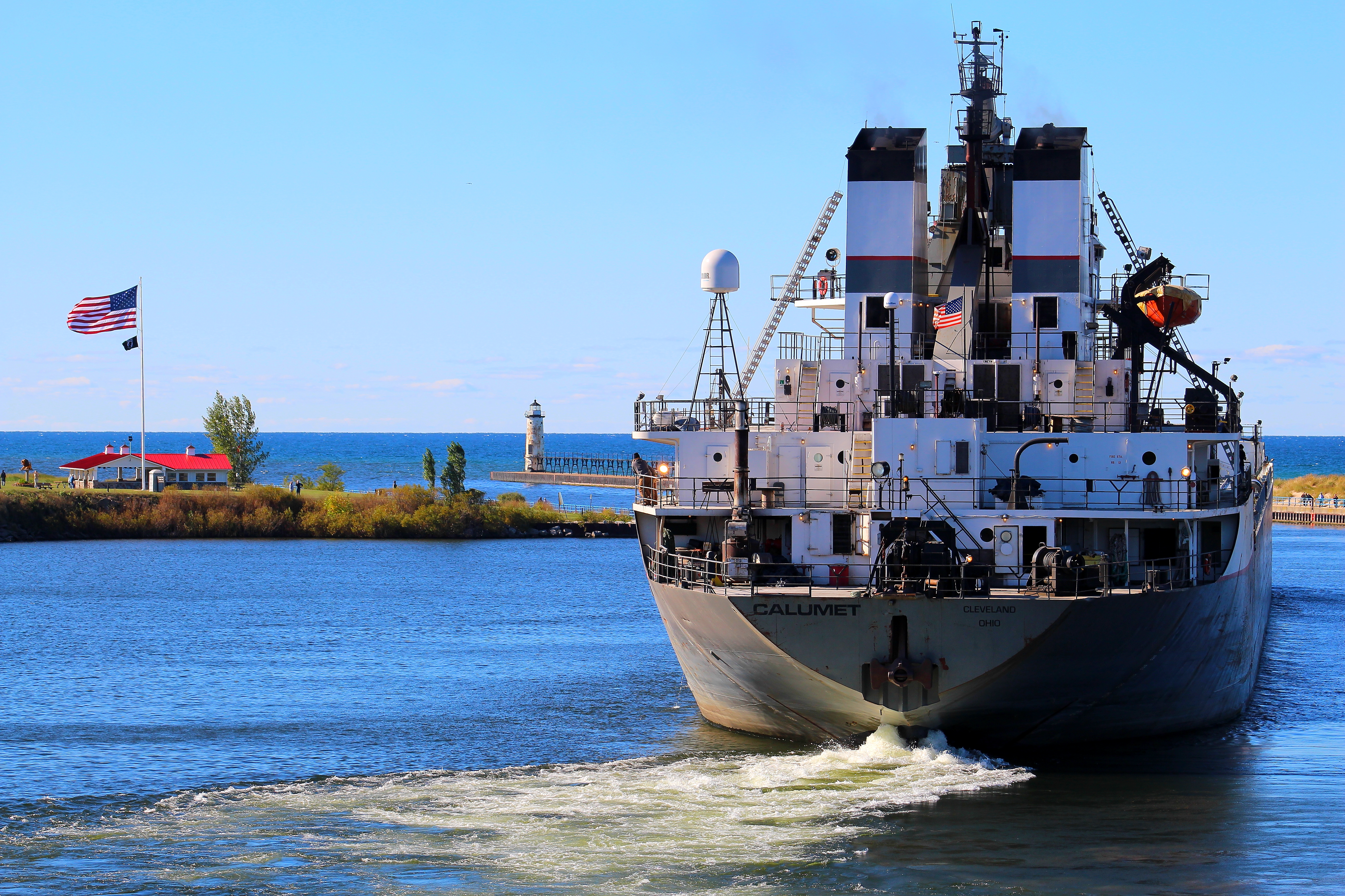 Freighter Calumet exiting the Manistee River Channel showing the bow thrusters  churning up the water to navigate the turn in the