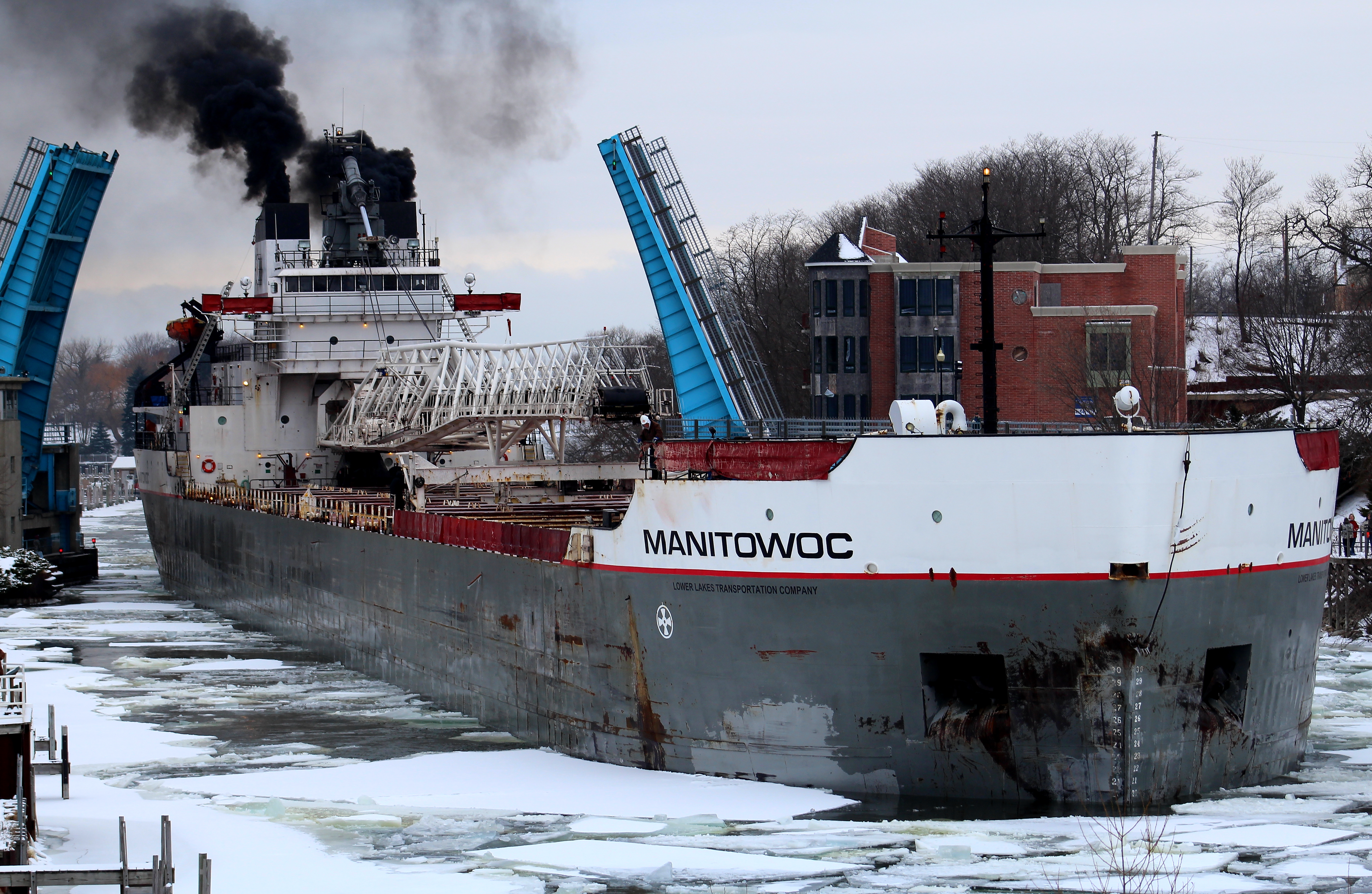 Freighter Manitowoc going through Maple Street Bridge in the winter with ice in the channel