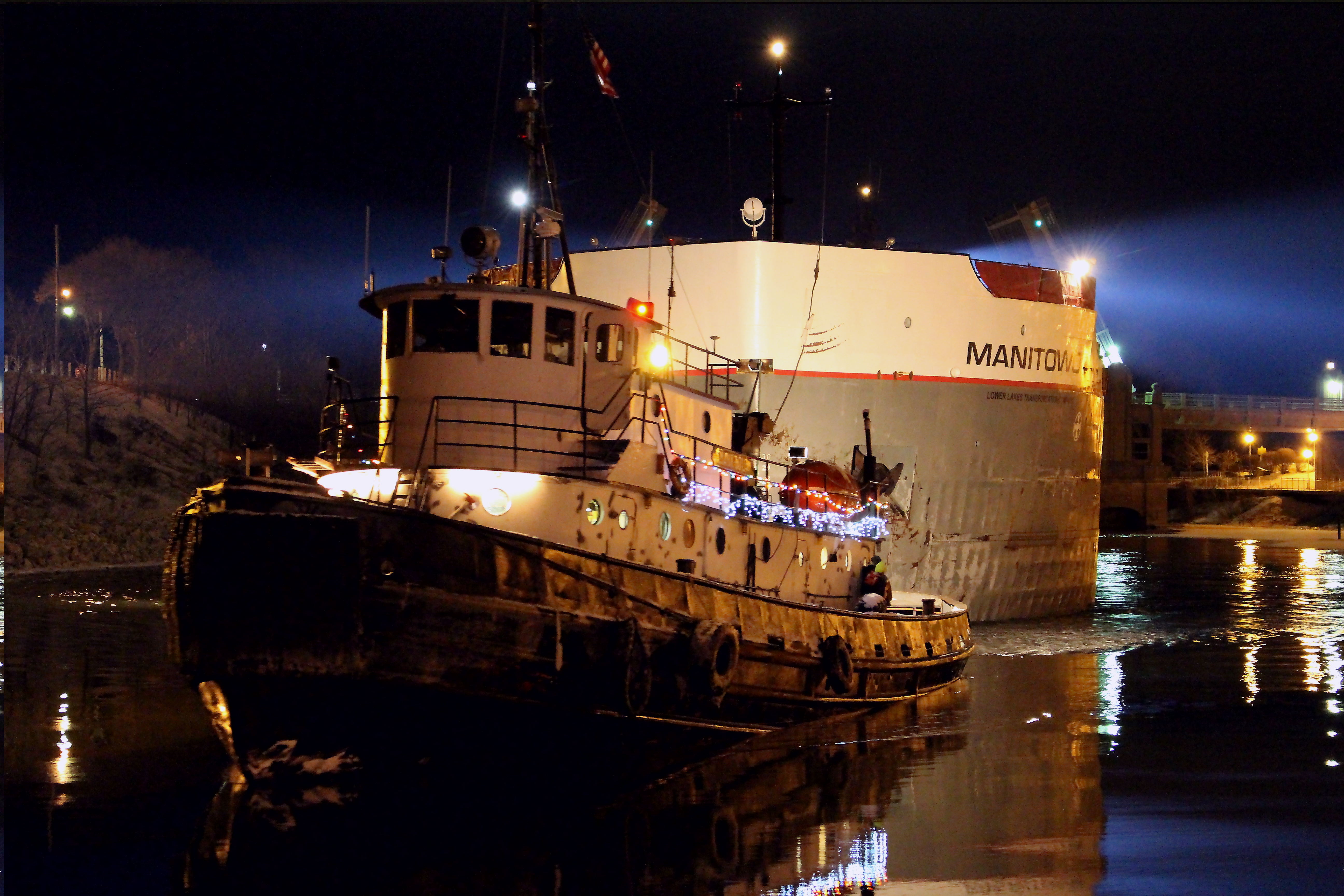 Freighter Manitowoc and Tug Boat seen at night in the Manistee River Channel