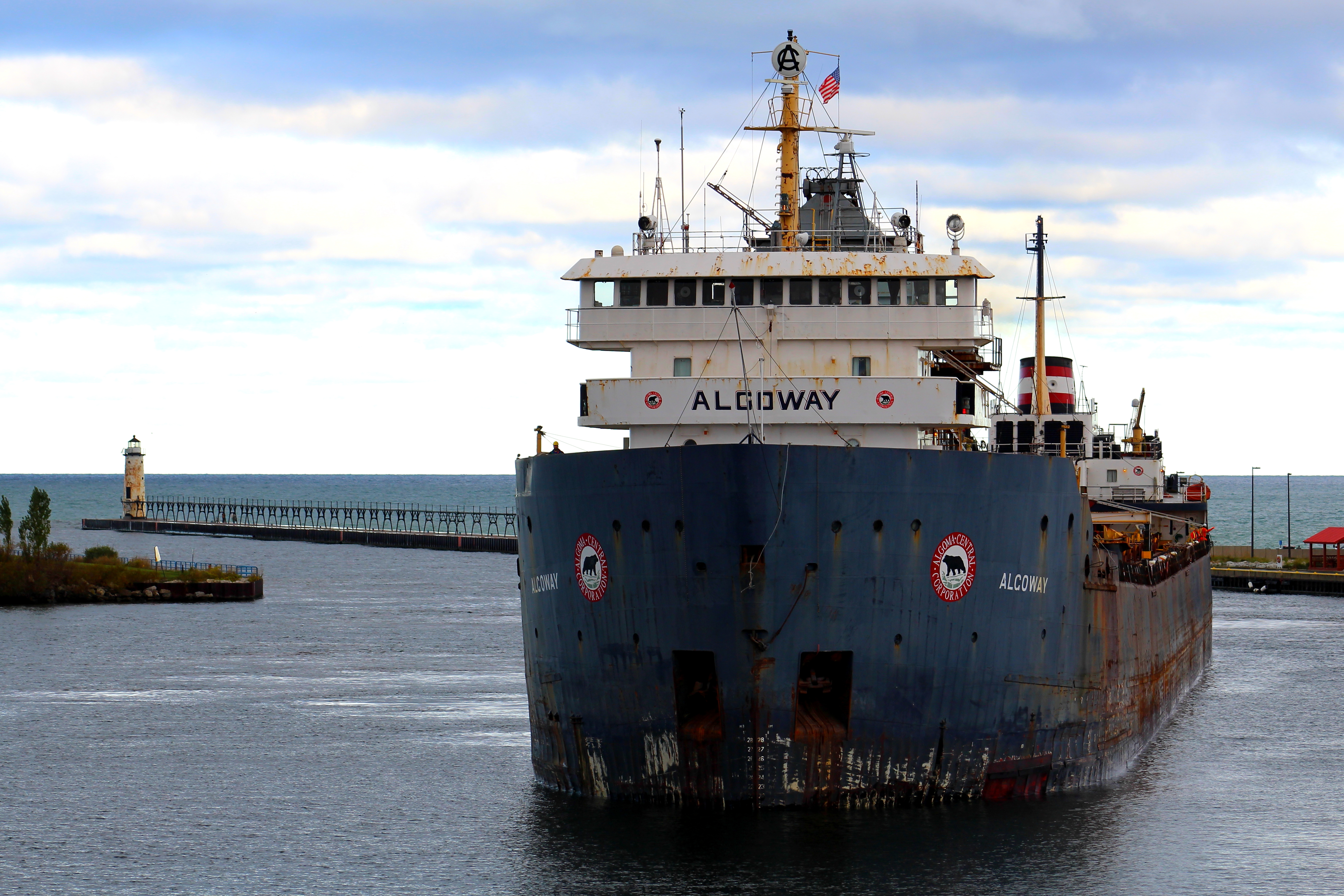 Freighter Algoway entering Manistee River Channel with the Fifth Avenue Lighthouse in the background