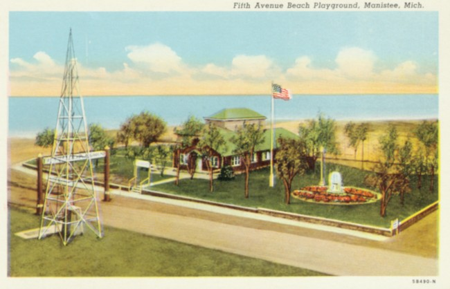Post card that reads Fifth Avenue Beach Playground, Manistee, Michigha that shows the former Northside Improvement Association building with a flag on a flag pole and a fountain
