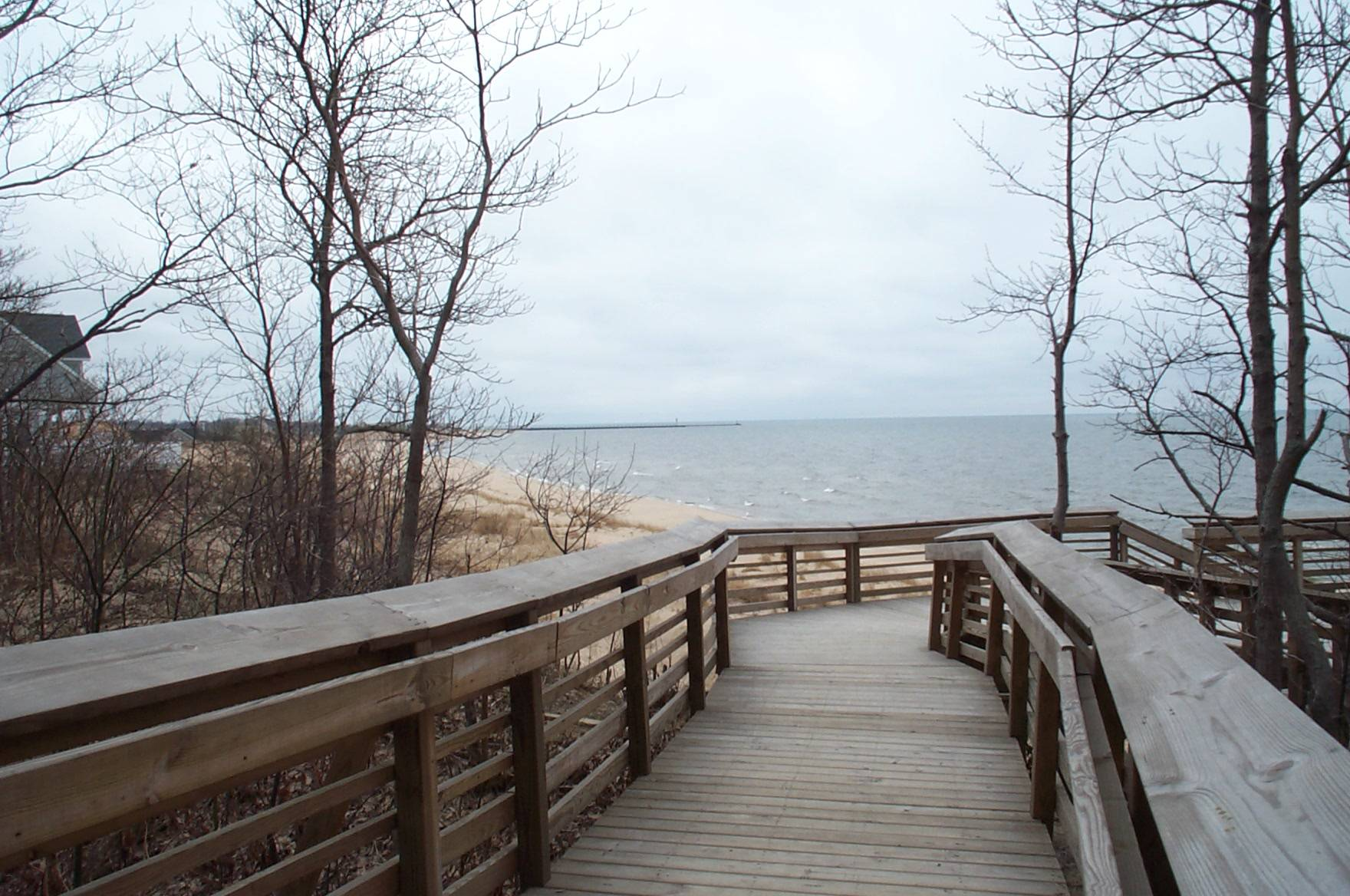 Photo taken from the wooden walkway to North Beach Access that overlooks the beach with a view of  Lake Michigan all the way to the Fifth Avenue Lighthouse