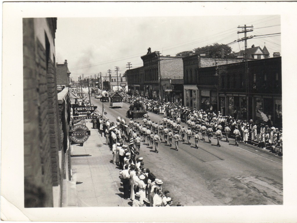 Photo taken from a second story window showing spectators on both sides of the street watch as a marching band performs behind floats going down River Street