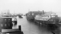 Historical photo of the Manistee River Channel with steamers docked and boat traffic on a calm day