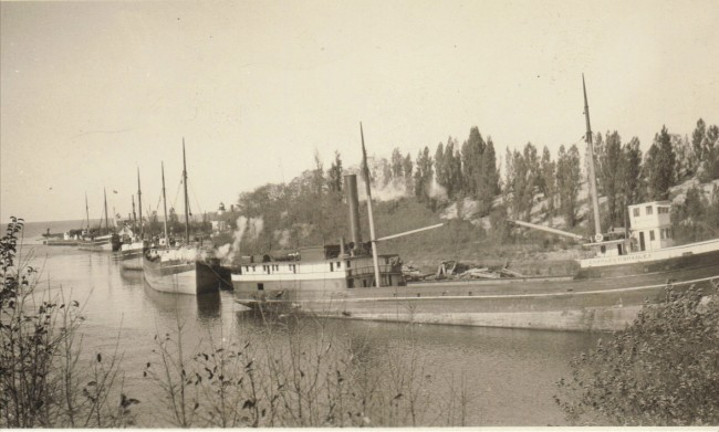 A line of schooners is seen in the Manistee River Channel in this photo taken circa 1926
